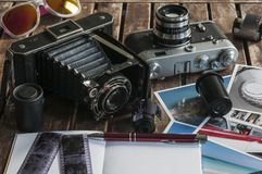 Retro photo cameras on a table. Old retro cameras on a table with photographs, negatives and films with Copy Space royalty free stock photos