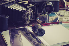 Retro photo cameras on a table. Old retro cameras on a table with photographs, negatives and films with Copy Space royalty free stock photography