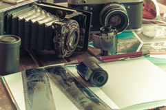 Retro photo cameras on a table. Old retro cameras on a table with photographs, negatives and films with Copy Space royalty free stock image