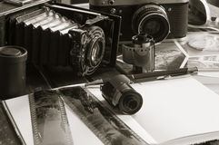 Retro photo cameras on a table. Old retro cameras on a table with photographs, negatives and films with Copy Space stock photo