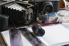 Retro photo cameras on a table. Old retro cameras on a table with photographs, negatives and films with Copy Space stock photography