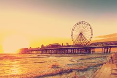 RETRO PHOTO FILTER EFFECT: Blackpool Central Pier at Sunset with Ferris Wheel, Lancashire, England UK stock photo