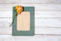 Photo frame with dry rose. Retro photo frame with dry rose on white wooden background Stock Images