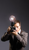 Retro photo journalist. Holding vintage camera with flash bulb Royalty Free Stock Image