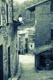 Retro photo of narrow street of old Catalan village. In Pyrenees. Rupit, Catalonia Royalty Free Stock Photo