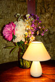 Retro photo. An old lamp.wildflowers.Unusual wall vintage background Stock Image