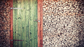 Retro photo of old rustic wooden door with firewood. Stock Image