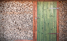 Retro photo of old rustic wooden door with firewood Stock Image
