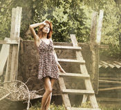Retro photo of a redhead woman in a dress in a village Royalty Free Stock Photo