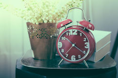 Retro photo style of modern alarm clock on tray with book and pl Stock Images