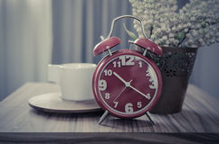 Retro photo style of red alarm clock on table Stock Image