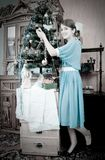 Retro photo of Teen girl decorating Christmas tre Royalty Free Stock Images