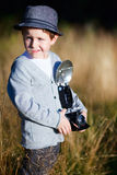 Retro photographer. Trendy small boy with retro camera photographing outdoors at sunny autumn day stock images