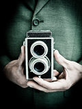 Retro photographer. With twin lens reflex style camera, closed, shooting from the hip Stock Image