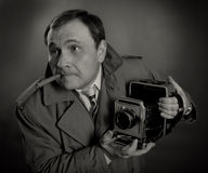 Retro Photographer. Black and white photo of a retro press photographer with an old camera and a sigar Stock Image