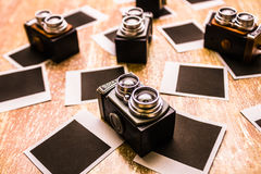 Retro photographic scene. Horizontal photograph on a collection of retro film cameras placed on old vintage instant photos. Retro photographic scene Stock Images