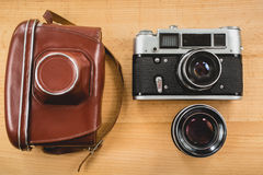 Retro photography set of camera, case and lens on wooden backgro Stock Image