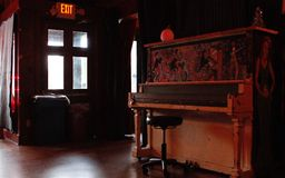 Retro piano bar interior in Athens, Georgia. An painted old piano sits in an empty, hardwood-floored room at a pub in Athens, Georgia Stock Image