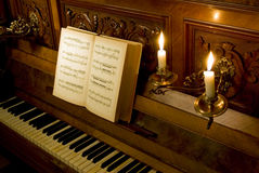 Retro piano with candle light. Retro Piano with ivory keys, open note book and candle lights Stock Photo