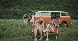 Retro picknicktijd twee charismatische dames die selfies zitting op de stoelen in het midden van gebied, achtergrondgroep nemen stock video