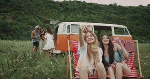 Retro picknicktijd voor groep jonge vrienden, in het midden van gebied twee dames die selfie zitting op picknickstoelen nemen stock footage