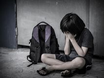 Sad Kid sitting on the floor with school bag waiting for parent. Retro picture with grain. Sad Kid sitting on the floor with school bag waiting for parent royalty free stock photo