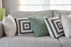 Retro pillows on cozy grey sofa in the living room Stock Image