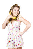 Retro pin up girl chatting on banana telephone Royalty Free Stock Image