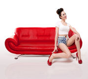 Retro Pin-up Girl On Red Leather Couch. Wearing shorts and stilettos and displaying her long legs Royalty Free Stock Images
