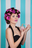 Retro pin up girl spraying perfume with hair rollers. And makeup Royalty Free Stock Photography