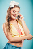 Retro pin up girl talking on mobile phone Royalty Free Stock Photos