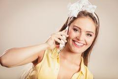 Retro pin up girl talking on mobile phone Royalty Free Stock Image