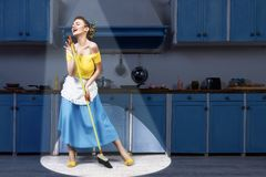 Retro pin up woman holding mop singing and cleaning. Retro pin up girl woman female housewife wearing yellow top, blue skirt and white apron holding mop singing royalty free stock photography