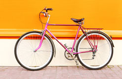 Retro pink bicycle stands over colorful orange Royalty Free Stock Images