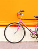 Retro pink bicycle stands over colorful orange background Stock Images