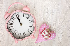 Retro pink clock and soft pink heart with word WISH on wooden ba Royalty Free Stock Images