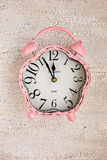 Retro pink clock on wooden background, top view Stock Images