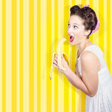 Retro pinup girl eating banana in 1950s fashion Royalty Free Stock Image