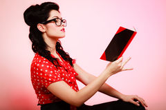 Retro. Pinup girl in eyeglasses reading book. Retro. Stylish woman student or teacher in eyeglasses reading book on pink. Brunette girl in pinup style. Education Stock Photo