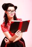 Retro. Pinup girl in eyeglasses reading book Stock Image