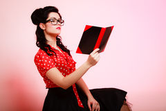 Retro. Pinup girl in eyeglasses reading book Royalty Free Stock Photos