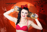 Retro pinup girl holding old wooden skateboard. Retro skate girl holding old grunge skateboard on rusty red texture background Stock Photos