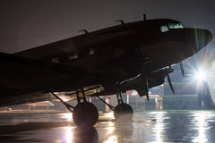 Retro plane on the rainy night. At the airport stock photography