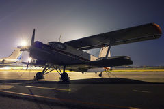 Retro plane on the summer night. At the airport stock image