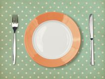 Retro plate with fork and knife on polka dot Royalty Free Stock Photography