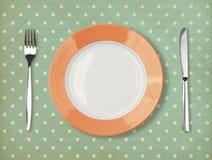 Retro- Platte mit Gabel und Messer auf Tupfen Lizenzfreie Stockfotografie