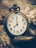 Retro pocket watch with antique number is showing 8 o'clock on wooden background. Stock Photos
