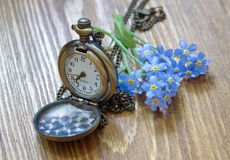 Retro pocket watch with forget me nots lying on the wooden table Stock Images