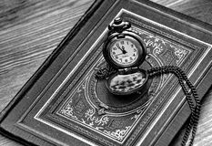 Retro pocket watch lying on the old book with ornaments Stock Images