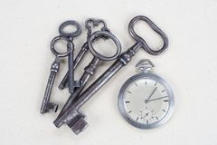 Retro pocket watch and old vintage key. A white textured background Royalty Free Stock Photos